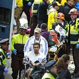 Medical workers aid injured people at the finish line of the 2013 Boston Marathon following an explosion Monday, April 15, 2013 in Boston. Two bombs exploded near the finish line of the marathon on Monday, killing at least two people, injuring at least 22 others and sending authorities rushing to aid wounded spectators.
