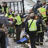 Medical workers aid injured people at the finish line of the 2013 Boston Marathon following explosions in Boston, Monday, April 15, 2013. Two explosions shattered the euphoria of the Boston Marathon finish line on Monday, sending authorities out on the course to carry off the injured while the stragglers were rerouted away from the smoking site of the blasts. (AP Photo/Charles Krupa)