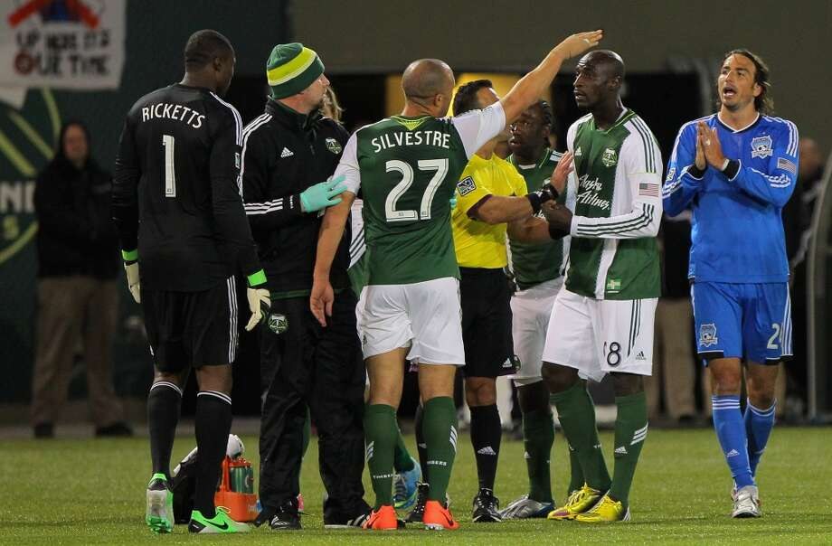 Referee Hilario Grajeda seperates Mikael Silvestre #27 of the Portland Timbers and Alan Gordan #24 of the San Jose Earthquakes after Gordon received his second yellow card and resulting red card for a foul on Silvestre in the 69th minute at JELD-WEN Field on April 14, 2013 in Portland, Oregon. The Timbers defeated the Earthquakes 1-0.