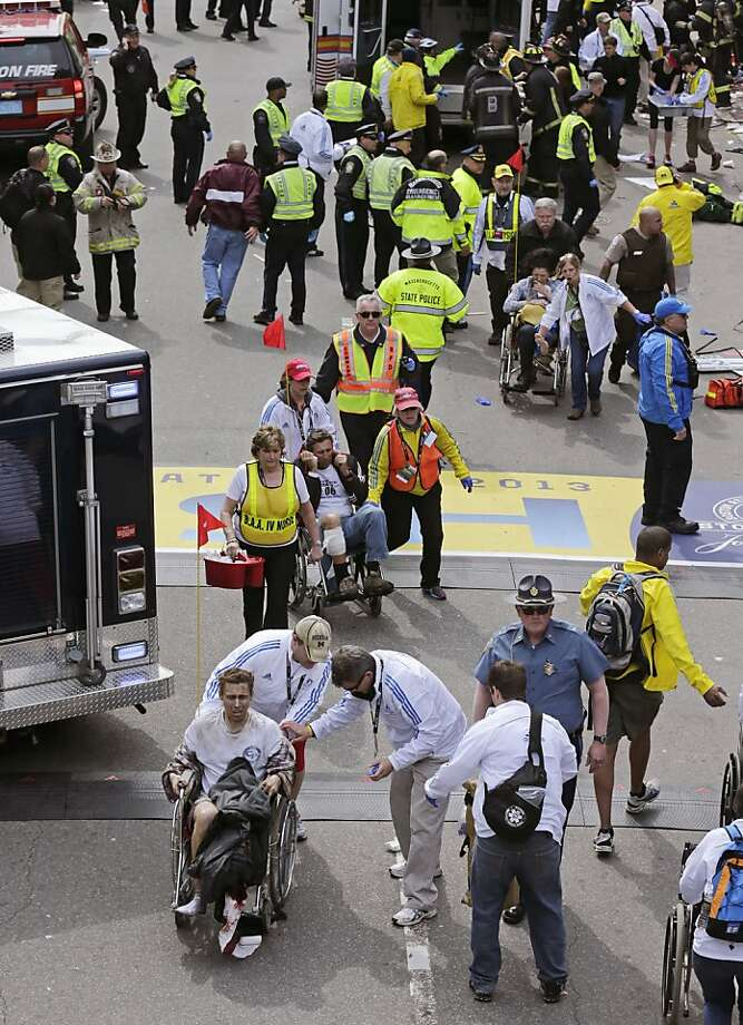 Medical workers aid injured people at the finish line of the 2013 Boston Marathon following an explosion in Boston, Monday, April 15, 2013. Two explosions shattered the euphoria of the Boston Marathon finish line on Monday, sending authorities out on the course to carry off the injured while the stragglers were rerouted away from the smoking site of the blasts. (AP Photo/Charles Krupa) Photo: Charles Krupa, Associated Press