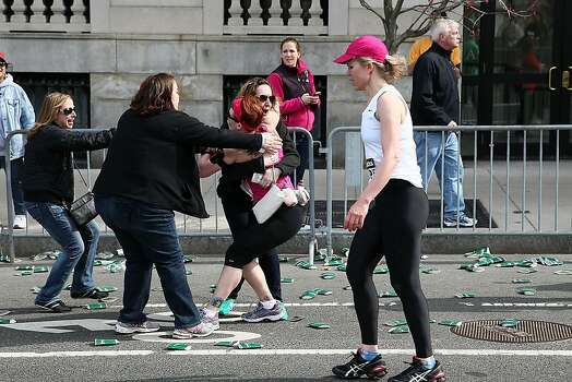 BOSTON, MA - APRIL 15:  A runner embraces another woman near Kenmore Square after two bombs exploded during the 117th Boston Marathon on April 15, 2013 in Boston, Massachusetts. Two people are confirmed dead and at least 23 injured after two explosions went off near the finish line to the marathon.  (Photo by Alex Trautwig/Getty Images) Photo: Alex Trautwig, Getty Images