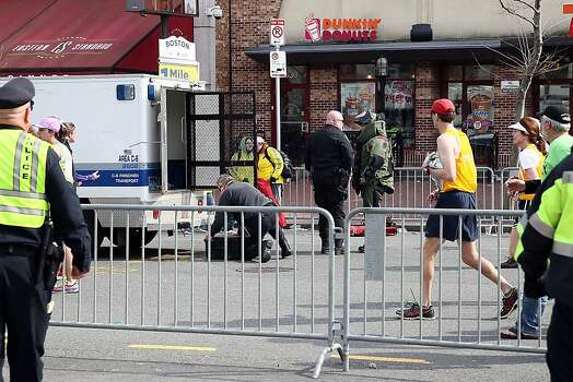 BOSTON, MA - APRIL 15:  Members of the bomb squad investigate a suspicious item on the road as runners pass near Kenmore Square after two bombs exploded during the 117th Boston Marathon on April 15, 2013 in Boston, Massachusetts. Two people are confirmed dead and at least 23 injured after two explosions went off near the finish line to the marathon.  (Photo by Alex Trautwig/Getty Images) Photo: Alex Trautwig, Getty Images