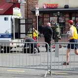 BOSTON, MA - APRIL 15:  Members of the bomb squad investigate a suspicious item on the road as runners pass near Kenmore Square after two bombs exploded during the 117th Boston Marathon on April 15, 2013 in Boston, Massachusetts. Two people are confirmed dead and at least 23 injured after two explosions went off near the finish line to the marathon.  (Photo by Alex Trautwig/Getty Images)