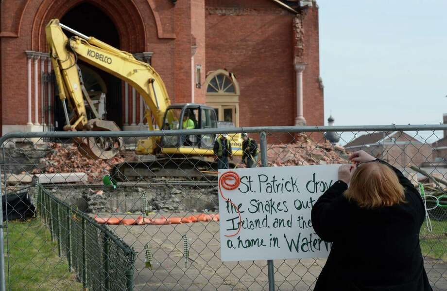 "Donna Wellworth posts a sign on the fence as demolition work continues Monday, April 15, 2013, at St. Patrick's Church in Watervliet, N.Y.  The sign says ""St. Patrick drove the snakes out of Ireland, and they found a home in Watervliet."" (Skip Dickstein/Times Union) Photo: SKIP DICKSTEIN / 10021967A"