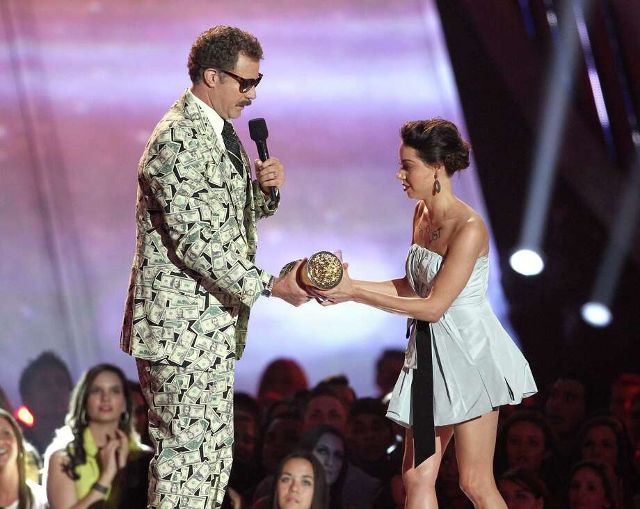 This April 14, 2013 photo shows actress Aubrey Plaza, right, as she tries to take away an award presented to Will Ferrell during the MTV Movie Awards in Culver City, Calif.  Plaza approached the stage as Ferrell made his acceptance speech after winning the Comedic Genius award. (Photo by Matt Sayles/Invision /AP) Photo: Matt Sayles