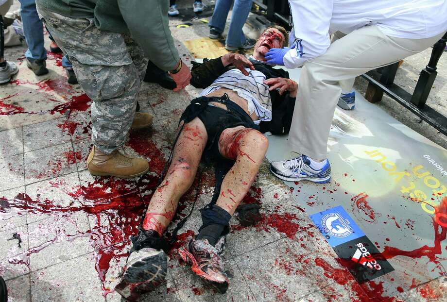 BOSTON - APRIL 15: (EDITOR'S NOTE: THIS IMAGE CONTAINS GRAPHIC CONTENT) A victim of the first explosion is helped on the sidewalk of Boylston Street, after two explosions went off near the finish line of the 117th Boston Marathon. (Photo by John Tlumacki/The Boston Globe via Getty Images) Photo: Boston Globe, Wire / 2013 - The Boston Globe
