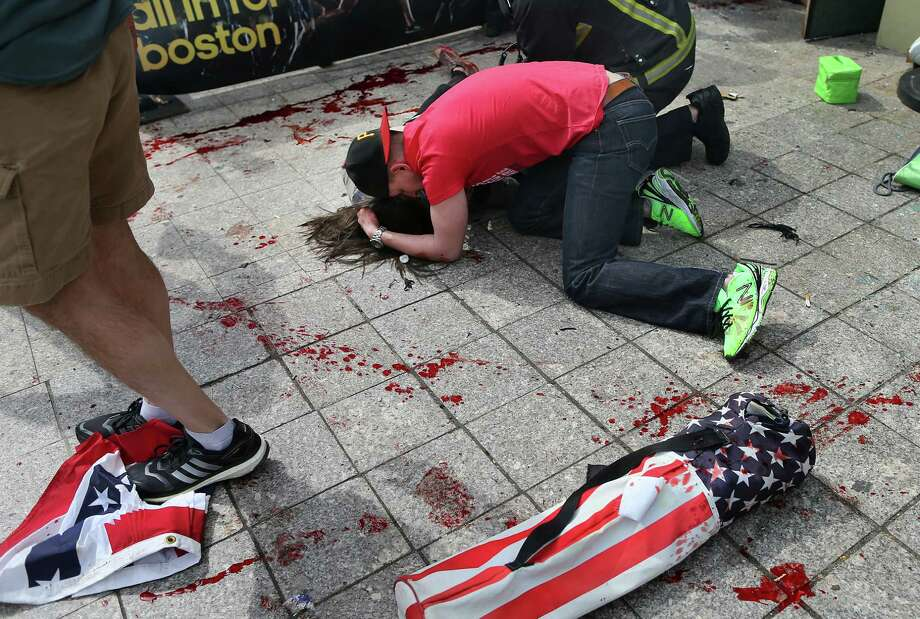 BOSTON - APRIL 15: (EDITOR'S NOTE: THIS IMAGE CONTAINS GRAPHIC CONTENT) A man comforts a victim on the sidewalk at the scene of the first explosion near the finish line of the 117th Boston Marathon. (Photo by John Tlumacki/The Boston Globe via Getty Images) Photo: Boston Globe, Wire / 2013 - The Boston Globe