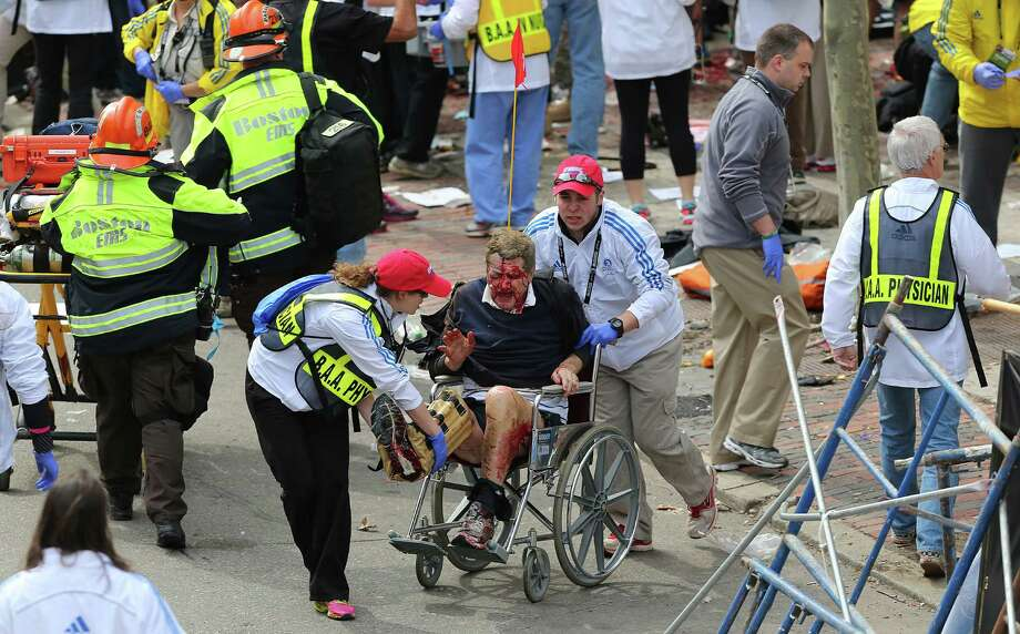 BOSTON - APRIL 15: (EDITOR'S NOTE: THIS IMAGE CONTAINS GRAPHIC CONTENT) A person who was injured in an explosion near the finish line of the 117th Boston Marathon is taken away from the scene in a wheelchair. Photo: Boston Globe, Getty Images / 2013 - The Boston Globe
