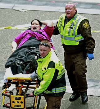 Medical workers aid an injured woman at the finish line of the 2013 Boston Marathon following two explosions there, Monday, April 15, 2013 in Boston. Two bombs exploded near the finish of the Boston Marathon on Monday, killing at least two people, injuring at least 23 others and sending authorities rushing to aid wounded spectators. (AP Photo/Charles Krupa) Photo: Getty Images