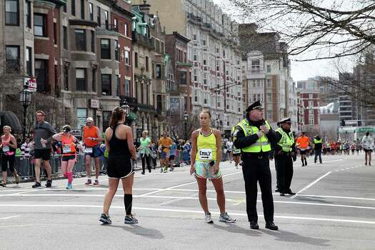 BOSTON, MA - APRIL 15:  Police and runners stand near Kenmore Square after two bombs exploded during the 117th Boston Marathon on April 15, 2013 in Boston, Massachusetts. Two people are confirmed dead and at least 28 injured after at least two explosions went off near the finish line to the marathon. Photo: Alex Trautwig, Getty Images / 2013 Getty Images