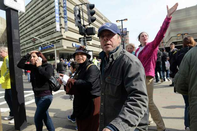BOSTON, MA - APRIL 15:  People look on at the corner of Stuart and Dartmouth St., near the finish line after two bombs exploded during the 117th Boston Marathon on April 15, 2013 in Boston, Massachusetts. Two people are confirmed dead and at least 28 injured after at least two explosions went off near the finish line to the marathon. Photo: Darren McCollester, Getty Images / 2013 Getty Images