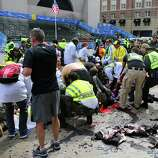 BOSTON - APRIL 15: The injured are helped at the scene of the first explosion on Boylston Street near the finish line of the Boston Marathon.