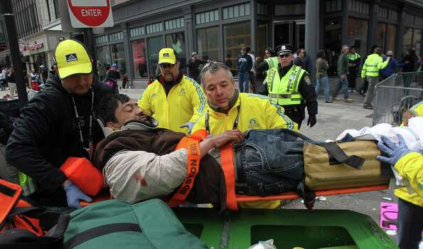 BOSTON - APRIL 15: Emergency personnel transport a man transported from the scene on Boylston Street. People react after two explosions went off near the finish line of the 117th Boston Marathon on April 15, 2013. Photo: Boston Globe, Getty Images / 2013 - The Boston Globe