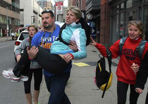 BOSTON - APRIL 15: A woman is carried from the scene on Exeter Street after two explosions went off on Boylston Street near the finish line of the 117th Boston Marathon on April 15, 2013. Photo: Boston Globe, Getty Images / 2013 - The Boston Globe