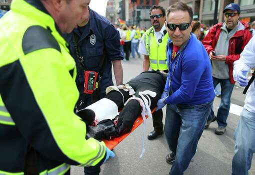 BOSTON - APRIL 15: (EDITOR'S NOTE: THIS IMAGE CONTAINS GRAPHIC CONTENT) An injured person is carried from the scene of the first explosion near the finish line of the 117th Boston Marathon. Photo: Boston Globe, Getty Images / 2013 - The Boston Globe