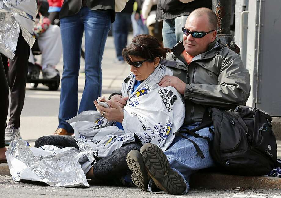 Chris Darmody, right, holds his wife Sue in Boston, Monday, April 15, 2013. Chris says he was waiting for Sue when an explosion detonated near his location at the finish line of the Boston Marathon. The couple were later reunited after all runners were diverted from the course. (AP Photo/Michael Dwyer) Photo: Michael Dwyer, Associated Press