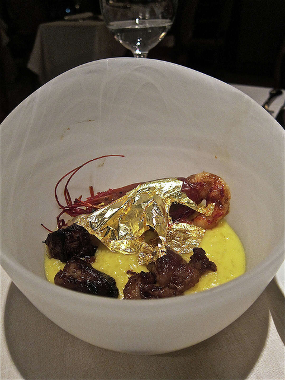 Risotto with bone marrow and whole prawn blanketed with edible gold leaf, at Ristorante Cavour