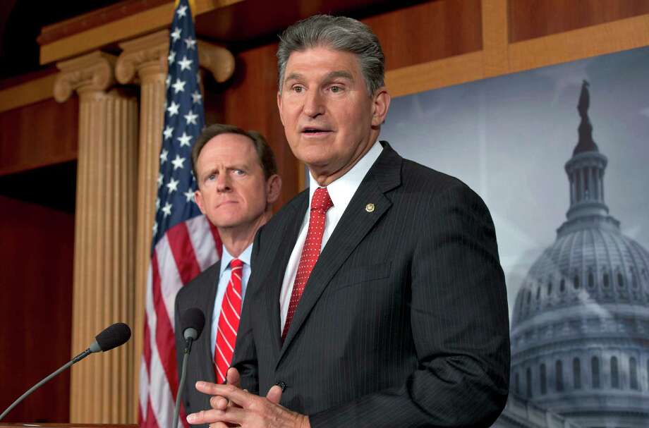 FILE - In this April 10, 2013 file photo, Sen. Joe Manchin, D-W.Va., right, accompanied by Sen. Patrick Toomey, R-Pa., announce that they have reached a bipartisan deal on expanding background checks to more gun buyers,, on Capitol Hill in Washington. The number of Republican senators who might back expanded background checks is now dwindling, threatening a bipartisan effort to subject more gun buyers to the checks. A vote on the compromise, the heart of Congress' gun control effort, is expected this week.  (AP Photo/J. Scott Applewhite, File) Photo: J. Scott Applewhite