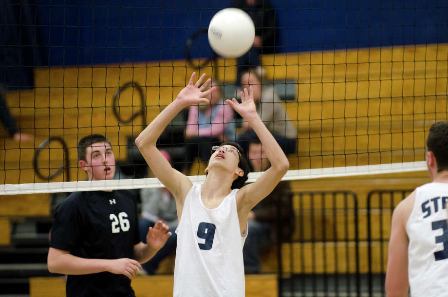 Staples' Harry Hlawitschka (9) sets the ball as Fairfield's Emilio Renzulli (26) watches the net during the boys volleyball game against Fairfield Ludlowe/Warde co-op at Staples High School in Westport on Monday, Apr. 15, 2013. Photo: Amy Mortensen / Connecticut Post Freelance