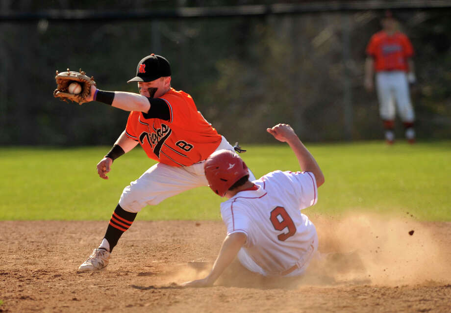 Greenwich's Liam O'Neil slides safely into second base beating the tag of Ridgefield shortstop Bryce Maher during their game at Greenwich High School on Monday, April 15, 2013. Greenwich won, 8-5. Photo: Jason Rearick / Stamford Advocate
