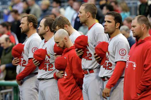 Members of the St. Louis Cardinals line up for a moment of silence for the bombings at the Boston Marathon the national anthem all wearing the number 42 in honor of Jackie Robinson before a baseball game against the Pittsburgh Pirates in  Pittsburgh Monday, April 15, 2013. Photo: AP