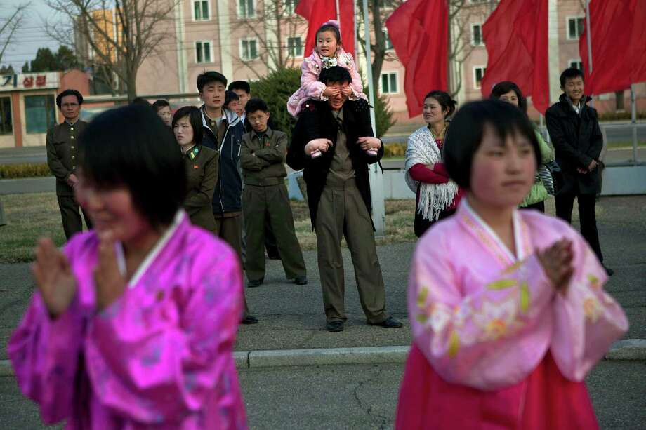 A North Korean child covers the eyes of her father as she sits on his shoulders watching mass folk dancing in front of Pyongyang Indoor Stadium in Pyongyang, North Korea, on Monday, April 15, 2013. Oblivious to international tensions over a possible North Korean missile launch, Pyongyang residents spilled into the streets Monday to celebrate a major national holiday, the birthday of their first leader, Kim Il Sung. (AP Photo/David Guttenfelder) Photo: David Guttenfelder