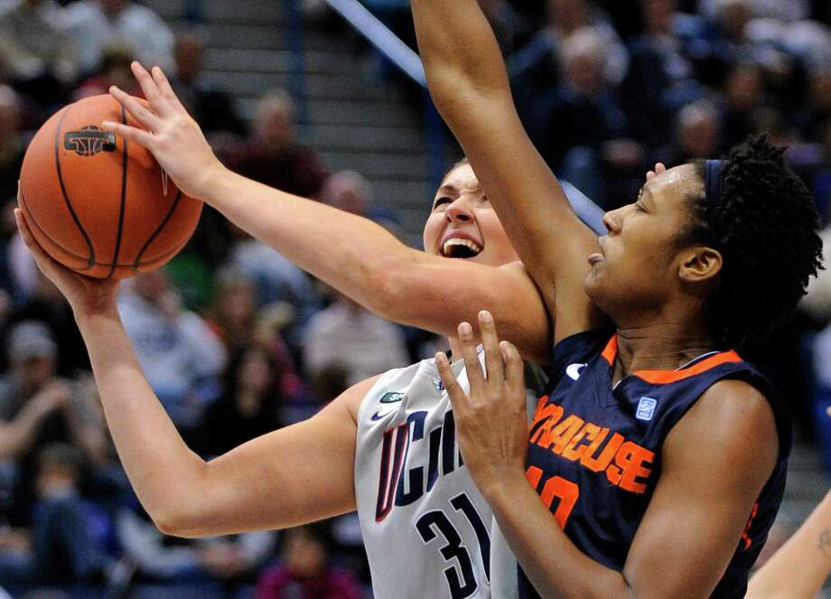 Connecticut's Stefanie Dolson, left, drives to the basket while being guarded by Syracuse's Kayla Alexander during the second half of an NCAA college basketball game in Hartford, Conn., Saturday, Jan. 19, 2013. Dolson scored a game-high 25 points in Connecticut's 87-62 victory. (AP Photo/Fred Beckham) Photo: Fred Beckham, Associated Press / FR153656 AP