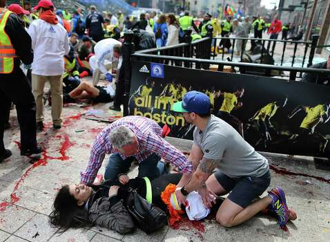 An injured woman is tended to at the finish line of the Boston Marathon,  in Boston, Monday, April 15, 2013. Two explosions shattered the euphoria of the Boston Marathon finish line on Monday, sending authorities out on the course to carry off the injured while the stragglers were rerouted away from the smoking site of the blasts.  MANDATORY CREDIT; BOSTON OUT Photo: The Boston Globe,  John Tlumacki