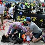 An injured woman is tended to at the finish line of the Boston Marathon,  in Boston, Monday, April 15, 2013. Two explosions shattered the euphoria of the Boston Marathon finish line on Monday, sending authorities out on the course to carry off the injured while the stragglers were rerouted away from the smoking site of the blasts.  MANDATORY CREDIT; BOSTON OUT