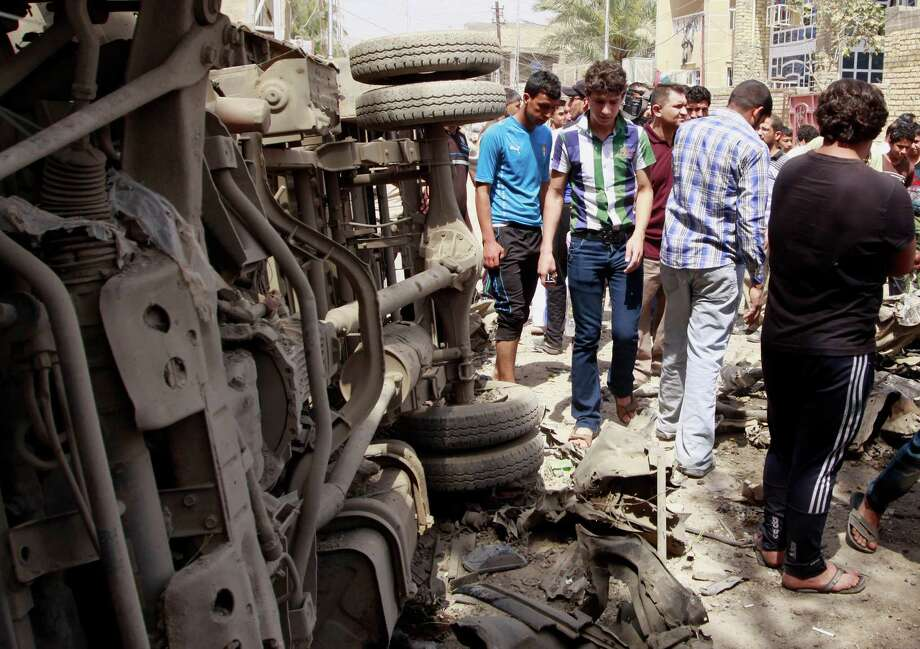 Civilians gather at the scene of a car bomb attack in east Baghdad's neighborhood of Kamaliya, Iraq, Monday, April 15, 2013. Less than a week before Iraqis in much of the country are scheduled to vote in the country's first elections since the 2011 U.S. troop withdrawal, a series of attacks across Iraq, many involving car bombs, has killed and wounded dozens of people, police said. (AP Photo/ Khalid Mohammed) Photo: Khalid Mohammed