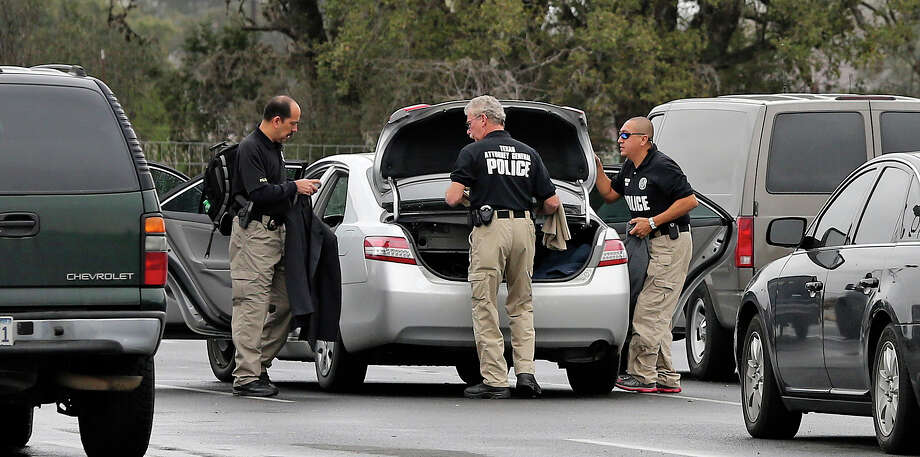 Agents stage in their car at the Scooter Store in New Braunfels as the FBI and other agencies conduct a search warrant at the facility on February 20, 2013. Photo: For The San Antonio Express-News