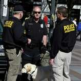 """Seattle Police officers, including Craig Williamson, center, and his explosives detection dog, """"Dennis"""" confer as during a patrol in downtown Seattle, Monday, April 15, 2013, in reaction to explosions at the Boston Marathon finish line earlier in the day. A Seattle Police blog posting said that although there was no indication of a direct threat to Seattle, officers would be increasing patrols and activity around the city. (AP Photo/Ted S. Warren)"""