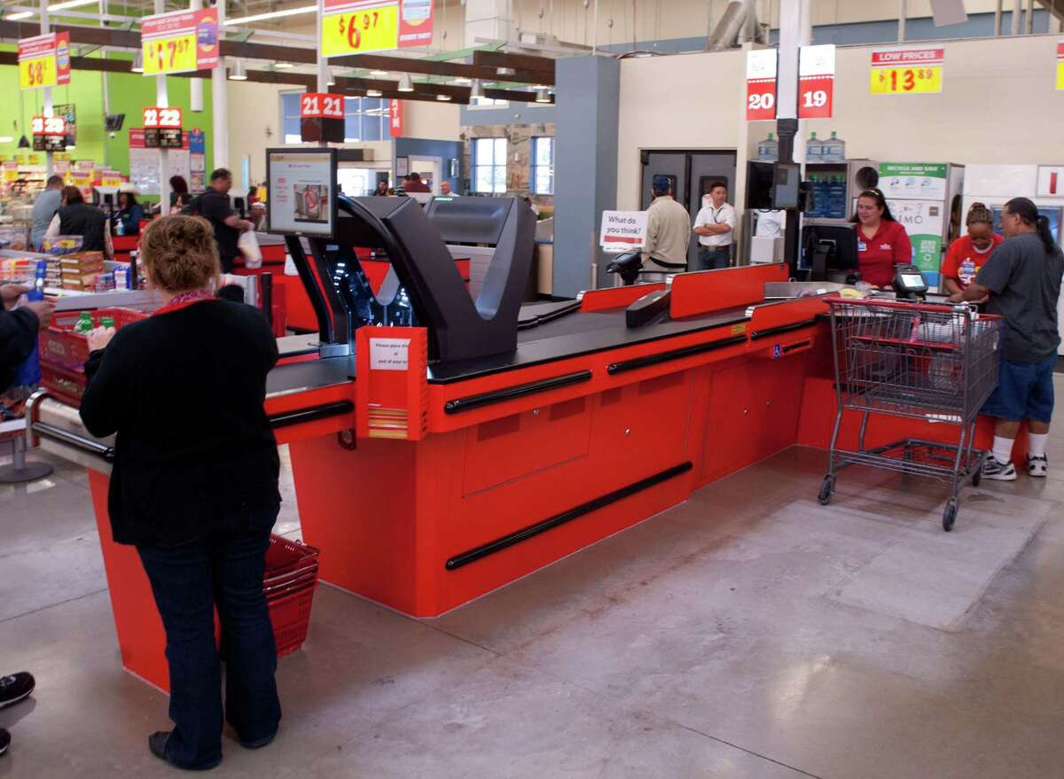 H-E-B cashiers focus on bagging produce and other items as customers unload their baskets with the company's Fast Scan checkout system at an H-E-B Plus store in San Antonio.