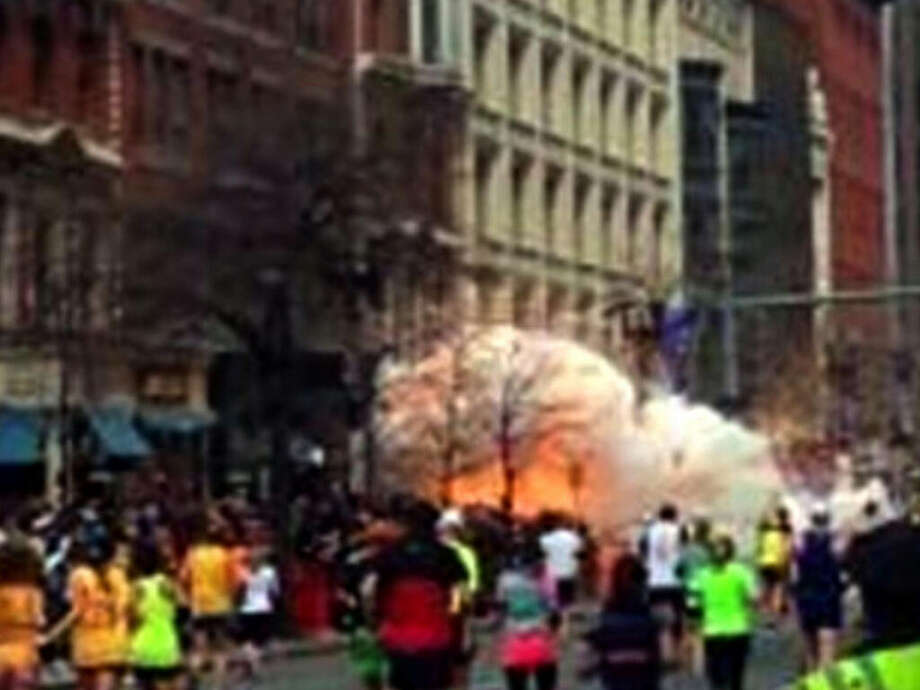 In this image from video provided by WBZ TV, spectators and runners run from what was described as twin explosions that shook the finish line of the Boston Marathon, Monday, April 15, 2013, in Boston.  Two explosions shattered the euphoria of the Boston Marathon finish line on Monday, sending authorities out on the course to carry off the injured while the stragglers were rerouted away from the smoking site of the blasts. (AP Photo/WBZTV) MANDATORY CREDIT / WBZ-TV