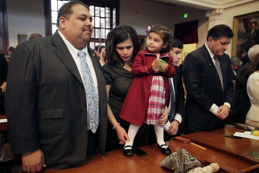 Cinco Guillen, 2, looks over at her father, Rep. Ryan Guillen, D-Rio Grande City, during the invocation at the start of the 83rd Texas Legislature at the State Capitol in Austin, Tuesday, Jan. 8, 2013. With them is his wife, Dalinda, (cq). On the right is Rep. Richard Pena Raymond, (tilde over n in Pena) and his son, Aren, (cq).