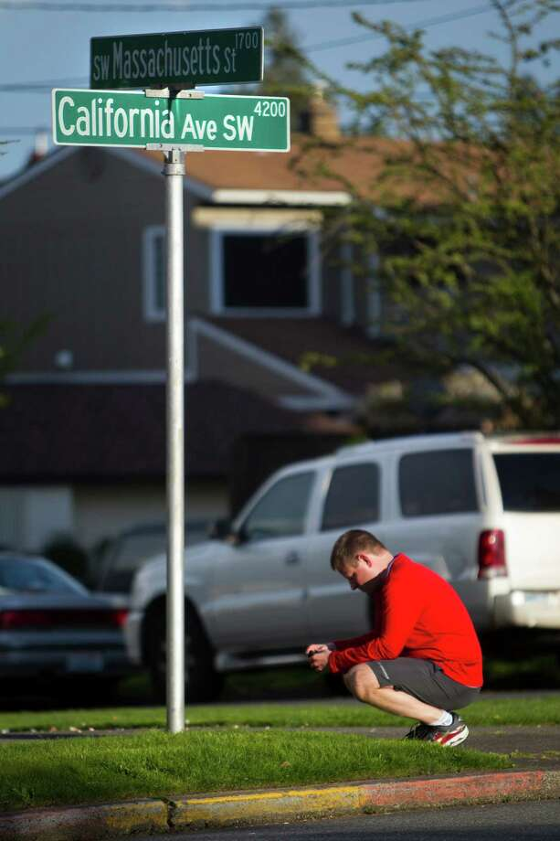 David Buchart kneels before the Southwest Massachusetts Street sign in West Seattle to pay his respects during an organized run to relieve the stresses of the Boston bombings Monday, April 15, 2013, in West Seattle. The group ran a loop from the West Seattle Runners store to Southwest Massachusetts Street and California Avenue Southwest intersection and back again. Photo: JORDAN STEAD / SEATTLEPI.COM