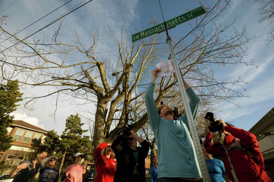 "Michael Wehling, in blue, hangs a sheet of paper with the Boston ""B"" on it to a street during an organized run to relieve the stresses of the Boston bombings Monday, April 15, 2013, in West Seattle. The group ran a loop from the West Seattle Runners store to Southwest Massachusetts Street and California Avenue Southwest intersection and back again. Photo: JORDAN STEAD / SEATTLEPI.COM"