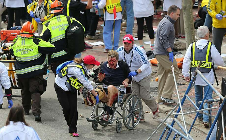 Medical workers aid injured people near the finish line of the Boston Marathon, where two explosions went off about four hours after the race's start. Photo: Boston Globe, Boston Globe Via Getty Images
