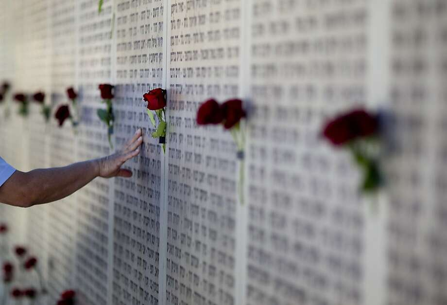 Mideast wars veteran touches the wall of names at the Armored Corps memorial for fallen soldiers after a ceremony marking the annual Memorial Day for soldiers and civilians killed in more than a century of conflict between Jews and Arabs, in Latrun near Jerusalem, Israel, Monday, April, 15,  2013. Israel says 23,085 security personnel have been killed since 1860, when Jews began moving back to the area. (AP Photo/Ariel Schalit) Photo: Ariel Schalit, Associated Press