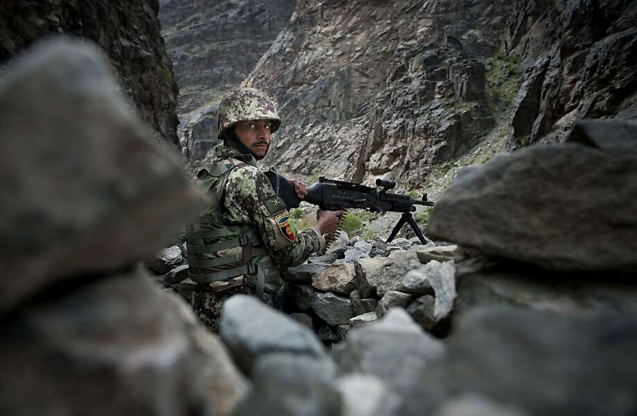 An Afghan Army soldier takes position on a road leading from Kabul to Jalalabad, Afghanistan, Monday, April 15, 2013. Despite questions about the ability of the Afghan army to successfully take the fight to the insurgency,  U.S. and coalition military officials say that the nascent force has made great strides in the past year and has surpassed many of their expectations. (AP Photo/Jawad Jalali) Photo: Jawad Jalali, Associated Press