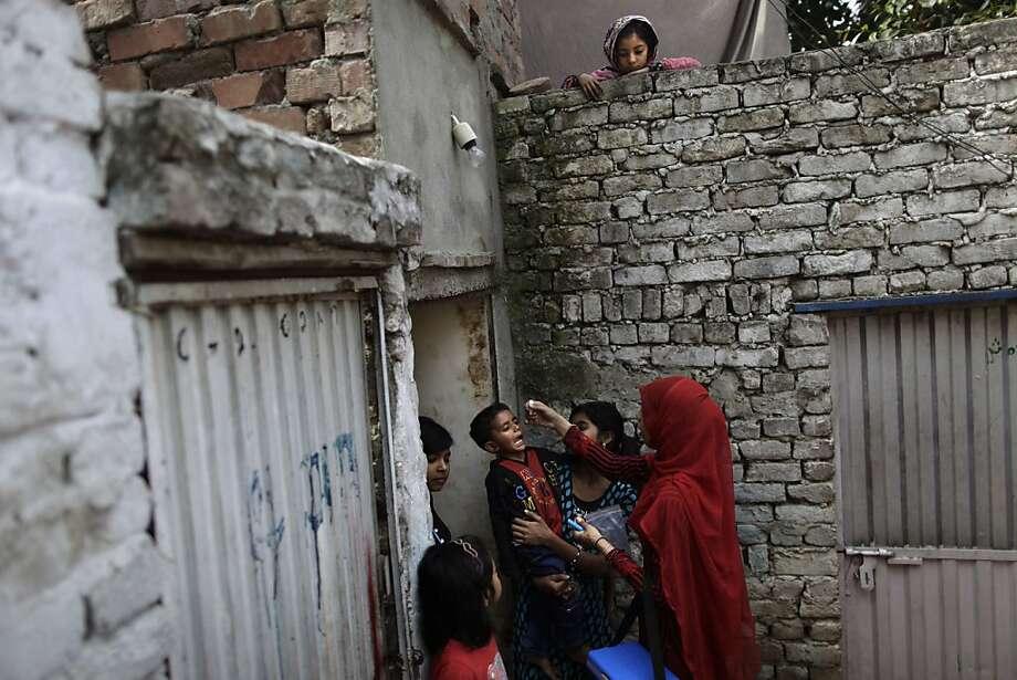 Una niña paquistaní, arriba, observa a la trabajadora de salud Salma Saleem que vacuna contra la poliomelitis a un niño en Islamabad, Pakistán el lunes 15 de abril de 2013. La Organización de Naciones Unidas considera que unos 240,000 niños han dejado de recibir vacunas por  las condiciones de inseguridad para trabajadores de salud. (AP Photo/Muhammed Muheisen) Photo: Muhammed Muheisen, Associated Press