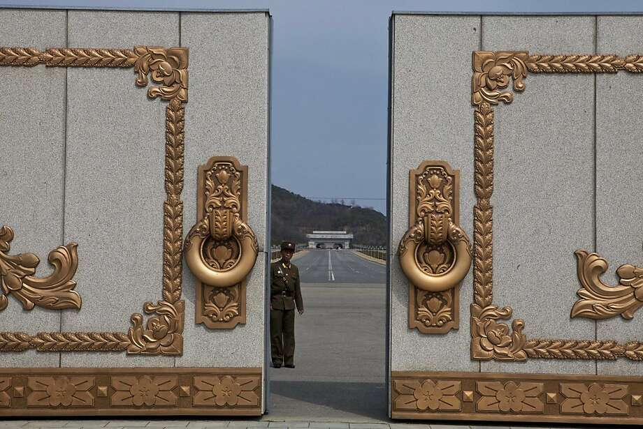 A North Korean soldier guarding the entrance to Pyongyang's Kumsusan mausoleum, where the bodies of the late leaders Kim Il Sung and Kim Jong Il lie embalmed, looks back through the doors of the main gate Monday, April 15, 2013. North Koreans turned out on Monday to mark the 101st birthday of Kim Il Sung. (AP Photo/David Guttenfelder) Photo: David Guttenfelder, Associated Press