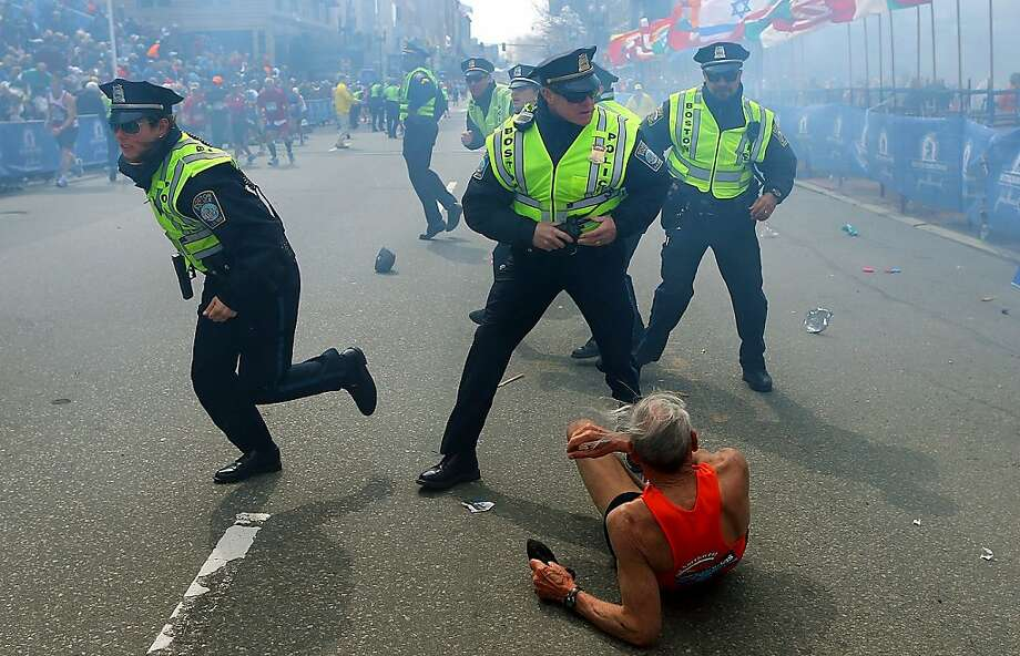 Bill Iffrig, 78, lies on the ground as police officers react to a second explosion at the finish line of the Boston Marathon in Boston, Monday, April 15, 2013. Iffrig, of Lake Stevens, Wash., was running his third Boston Marathon and near the finish line when he was knocked down by one of two bomb blasts. (AP Photo/The Boston Globe,  John Tlumacki) Photo: John Tlumacki, Associated Press