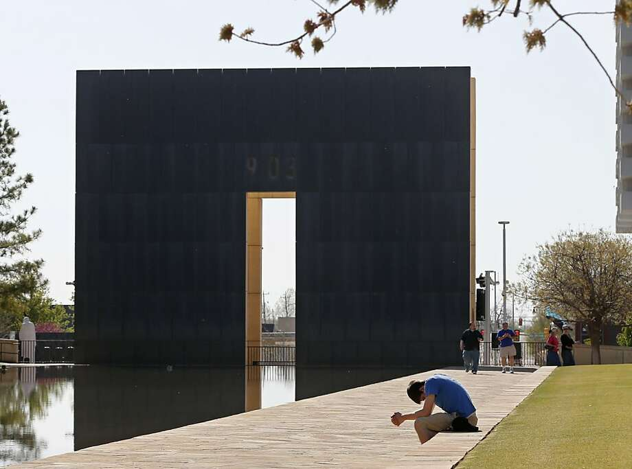 Shane Magness, a student at Oklahoma Christian University, bows his head in prayer for the victims of the Boston Marathon bombing, at the Oklahoma City National Memorial in Oklahoma City, Monday, April 15, 2013. On Friday, Oklahoma City will observe the 18th anniversary of the April 19, 1995, bombing of the Alfred P. Murrah Federal building that killed 168 people and injured hundreds more. (AP Photo/Sue Ogrocki) Photo: Sue Ogrocki, Associated Press