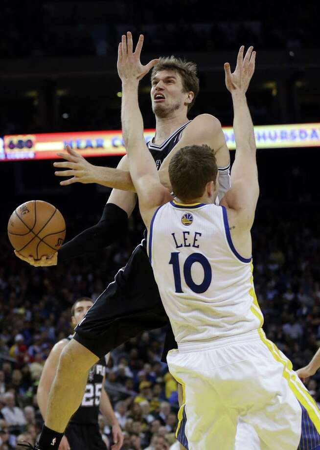 Spurs center Tiago Splitter (top) drives to the basket against David Lee of the Golden State Warriors. Photo: Marcio Jose Sanchez / Associated Press