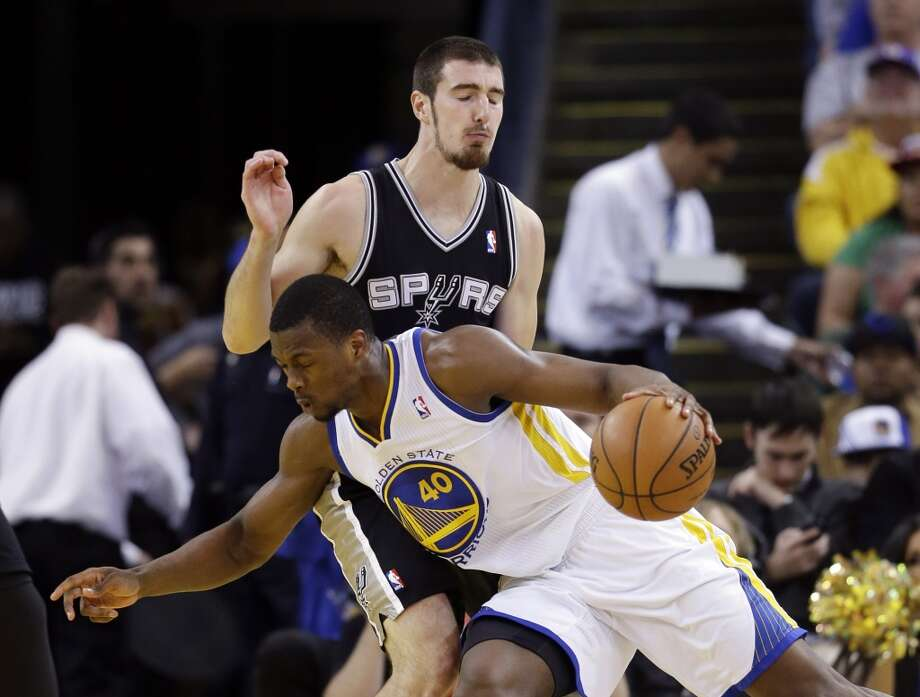 Golden State Warriors' Harrison Barnes (40) tries to dribble around the Spurs' Nando de Colo during the first half in Oakland, Calif., Monday, April 15, 2013.