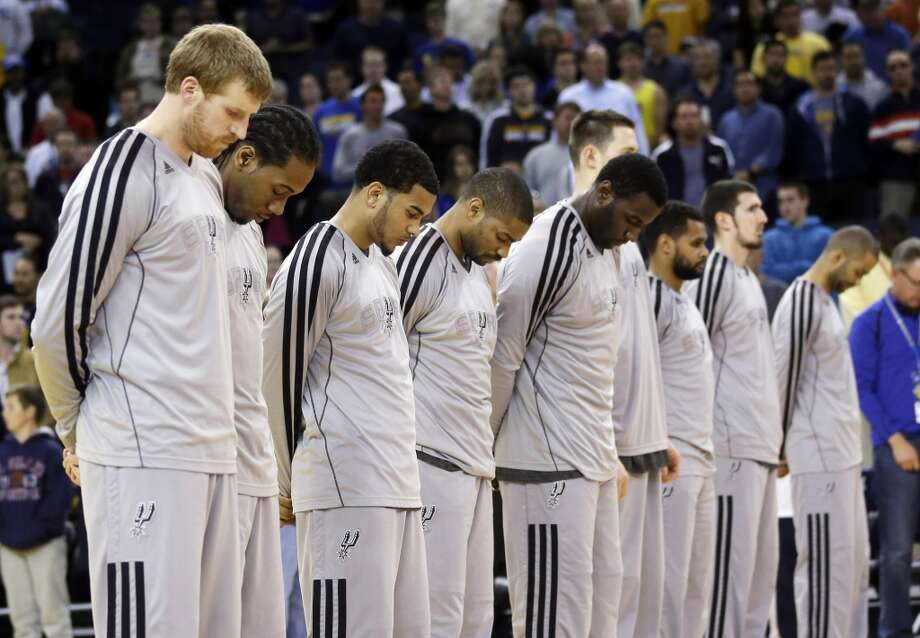 Members of the Spurs observe a moment of silence for victims of the Boston Marathon explosions before their game against the Golden State Warriors in Oakland, Calif., Monday, April 15, 2013.