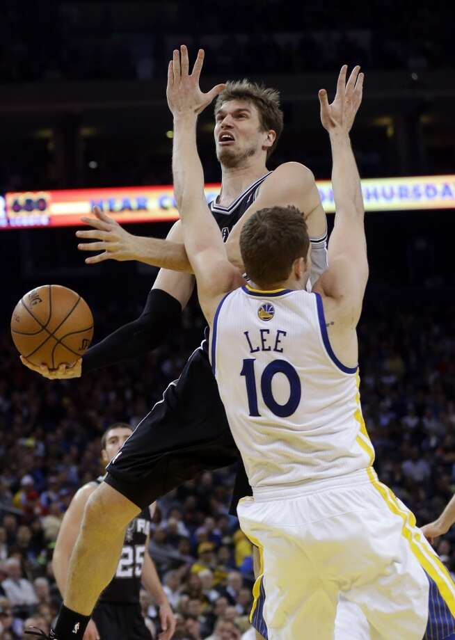 The Spurs' Tiago Splitter (top) drives to the basket as Golden State Warriors' David Lee (10) defends during the first half in Oakland, Calif., Monday, April 15, 2013.