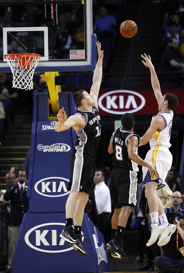 Klay Thompson (11) shoots over Aron Baynes (16) and Patty Mills (8) in the first quarter. The Golden State Warriors played the San Antonio Spurs at Oracle Arena in Oakland, Calif., on Monday, April 15, 2013. Photo: Carlos Avila Gonzalez, The Chronicle