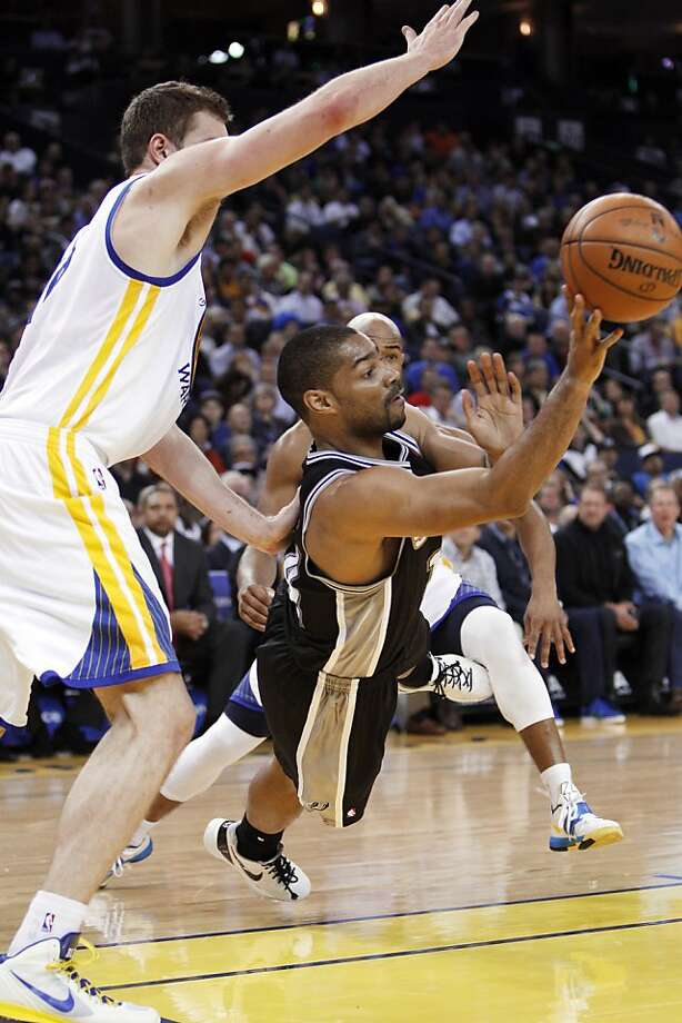 San Antonio's Gary Neal (14) passes the ball as he falls under the basket in the first half. The Golden State Warriors played the San Antonio Spurs at Oracle Arena in Oakland, Calif., on Monday, April 15, 2013. Photo: Carlos Avila Gonzalez, The Chronicle